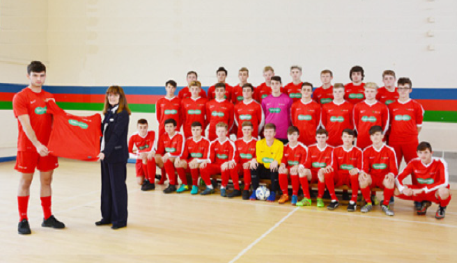 Susan Lewis, retail director at Specsavers: Presenting Coleg Sir Gâr Football Academy captain Liam Testino and his squad with the brand new kit sponsored by the Llanelli branch of the opticians